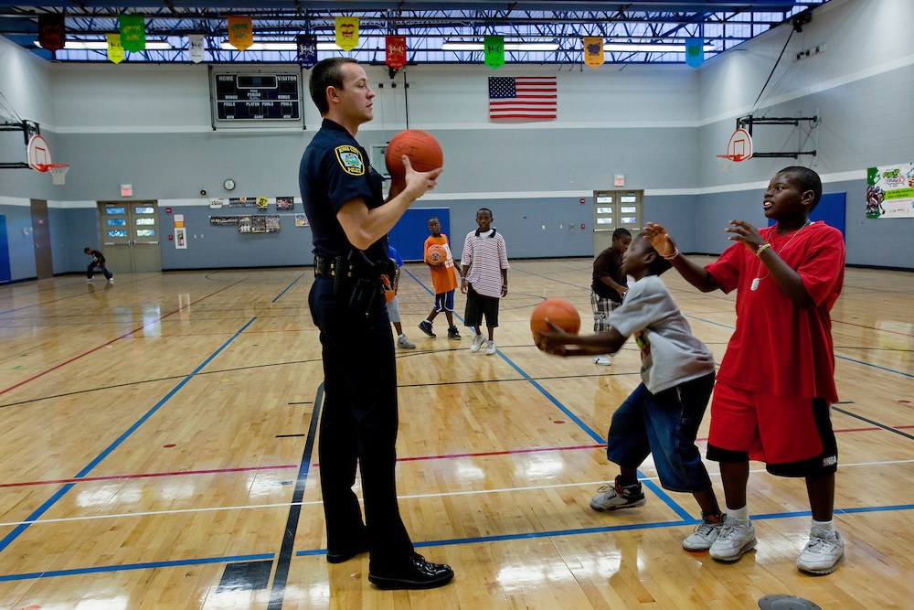 Crime Prevention Officer Jorey Bailey plays basketball with a few kids in an after school program at Grant Wood Elementary. Bailey's position with the Iowa City Police Department is directly related to the youth in the south east side of Iowa City. He tries to be present in the neighborhood as much as possible so the kids know who he is and aren't afraid of him. Many of the kids call him Officer Big Bird because of his height and friendly demeanor.